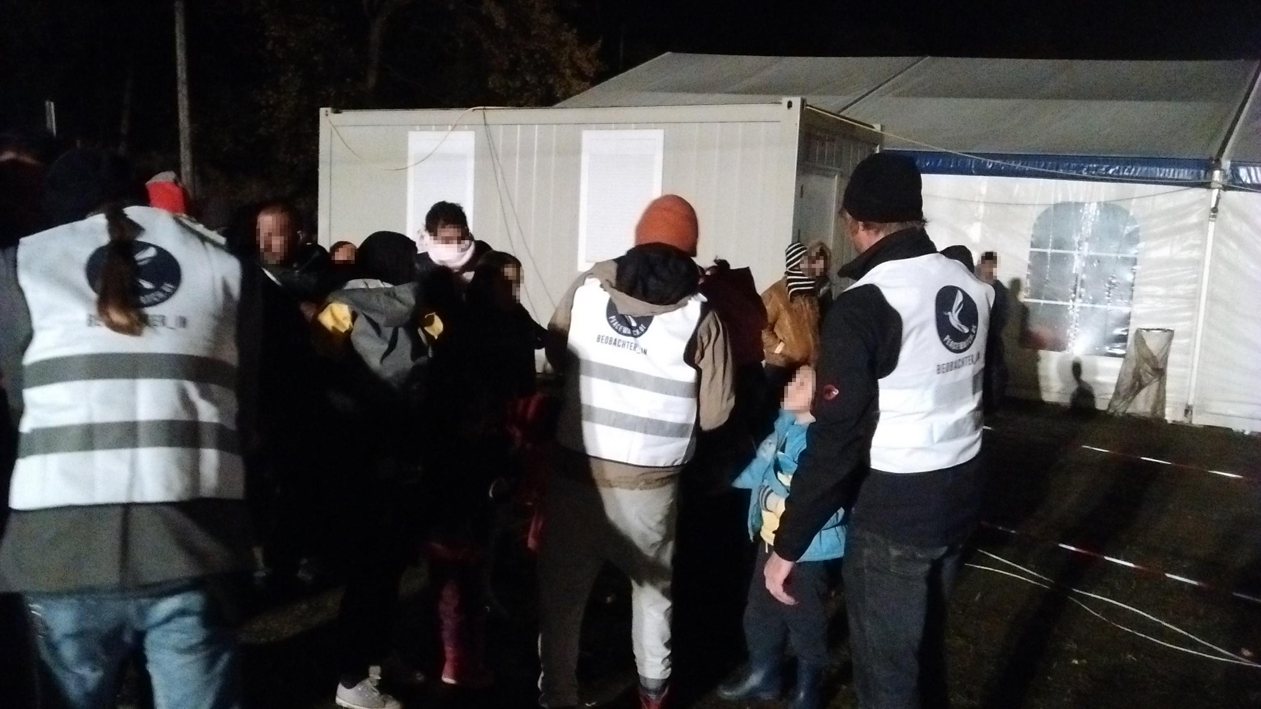 Freiwillige PeaceWatch-Helfer/innen erklären Asylsuchenden das Nummernsystem. Foto: PeaceWatch.de/M. Lindner